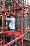 Homme se tirant vers le haut sur des constructions en métal Photographie stock libre de droits