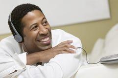 Homme se trouvant sur le sofa écoutant la musique sur la vue franche de CD de fin portative de lecteur photos libres de droits