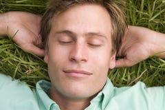 Homme se trouvant sur le sommeil d'herbe photos stock