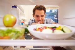 Homme semblant le réfrigérateur intérieur complètement de la nourriture et choisissant la salade Photographie stock libre de droits