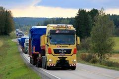 HOMME semi dans le convoi de camions large de charge Images libres de droits