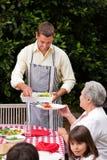 Homme servant sa mère à la table Images stock