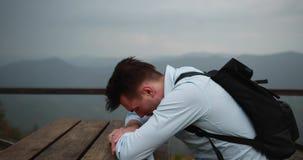 Homme seul dans les montagnes Le jeune homme bel se trouve sa tête sur les bras se reposant à la table avec la grande vue autour clips vidéos
