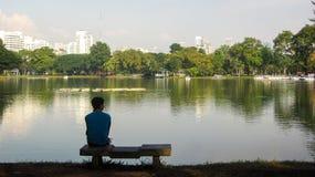 Homme seul devant le lac image stock