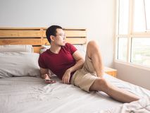 Homme seul jouant le sien téléphone dans sa chambre à coucher image libre de droits