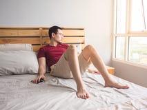 Homme seul jouant le sien téléphone dans sa chambre à coucher photographie stock libre de droits