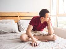 Homme seul jouant le sien téléphone dans sa chambre à coucher images libres de droits