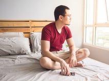 Homme seul jouant le sien téléphone dans sa chambre à coucher image stock