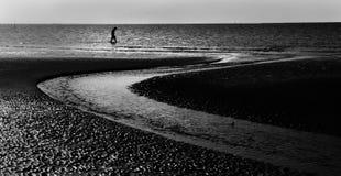 Homme seul marchant au bord de la mer Photo stock