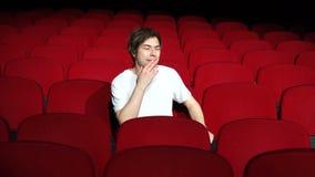 Homme seul s'asseyant dans le hall vide de cinéma et contrarié banque de vidéos