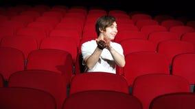 Homme seul s'asseyant et applaudissant dans le hall ou le théâtre vide de cinéma clips vidéos