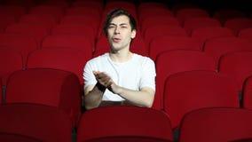 Homme seul s'asseyant et applaudissant dans le hall ou le théâtre vide de cinéma banque de vidéos