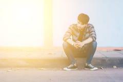 Homme seul s'asseyant sur la rue photo libre de droits