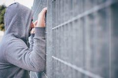 Homme seul se penchant contre la barrière photos stock