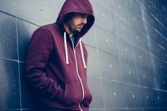 Homme seul se penchant contre un mur urbain images stock