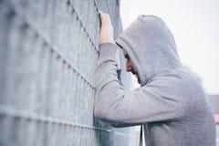Homme seul se penchant contre une barrière image libre de droits
