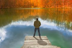 Homme seul se tenant au bord du petit pilier en bois regardant le lac Photo libre de droits