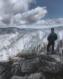 Homme seul se tenant et regardant fixement des montagnes, des nuages et la vallée en parc national de Yosemite image stock
