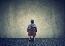 Homme seul sur la chaise contre le mur vide photo stock