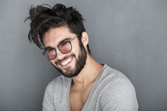 Homme sexy avec le sourire de barbe grand contre le mur Photos stock