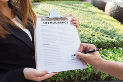 Homme signant le contrat d'assurance-vie Photographie stock
