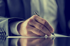 Homme signant un document ou écrivant la correspondance image libre de droits