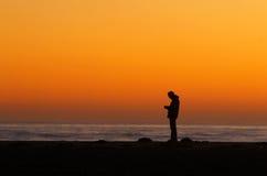 Homme silhouetté au coucher du soleil Photographie stock libre de droits