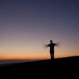 Homme silhouetté ondulant avec des bras dans le coucher du soleil Photos libres de droits