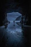 Homme simple se tenant à une entrée de caverne à côté de la mer Photographie stock libre de droits