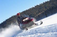 Homme Snowmobiling par la neige Photographie stock libre de droits