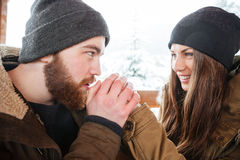 Homme soigneux chauffant ses mains d'amie en hiver Photos stock