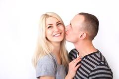 Homme soigneux embrassant son amie de sourire sur un fond blanc Photo stock