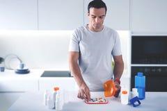 Homme soigneux prenant une pilule tout en prêtant l'attention à sa santé image stock