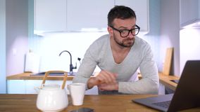 Homme somnolent barbu prenant le petit déjeuner dans la cuisine et à l'aide d'un ordinateur portable banque de vidéos