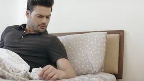 Homme somnolent se réveillant dans la chambre à coucher dans le matin Type beau arrêtant le réveil banque de vidéos