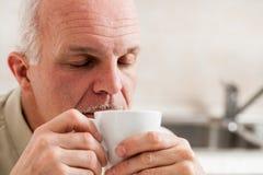 Homme somnolent tenant peu de tasse de café sur sa bouche Photo stock