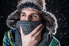 Homme songeur dans le chapeau et l'écharpe avec la neige Images stock