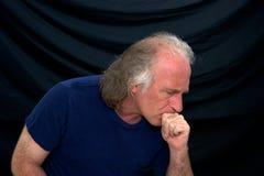 Homme songeur dans le T-shirt sur le noir Image libre de droits