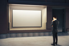 Homme songeur regardant le panneau d'affichage Image stock