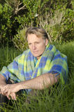Homme songeur s'asseyant dans l'herbe Photos stock