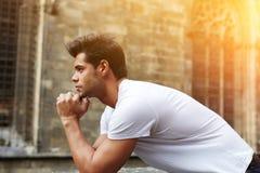 Homme songeur se tenant contre le bâtiment gothique photo stock