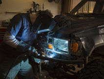 Homme soudant le pare-chocs d'un véhicule photo stock