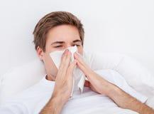 Homme soufflant son nez Image stock