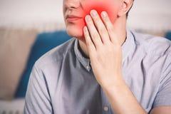 Homme souffrant d'un mal de dents à la maison images stock