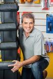 Homme soulevant les boîtes à outils empilées dans la boutique de matériel Photographie stock libre de droits