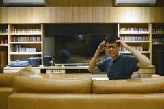 Homme soumis à une contrainte devant la TV vide dans le salon la nuit photographie stock