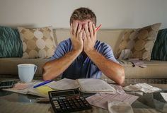 Homme soumis à une contrainte inquiété attirant à la maison calculant des dépenses d'impôts de mois avec des paiements de comptab images libres de droits