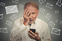Homme soumis à une contrainte jugeant le téléphone portable choqué avec le message reçu photos stock