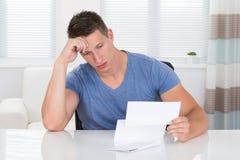 Homme soumis à une contrainte regardant le papier Photo libre de droits