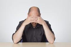 Homme soumis à une contrainte regardant vers le bas le bureau Photos libres de droits